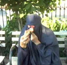 woman in burqa eating pizza