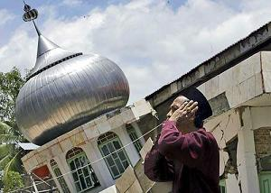 A Muslim offers prayers at a Fathur Rahman mosque, destroyed by an earthquake in Solok, Sumatra, Indonesia 2007.