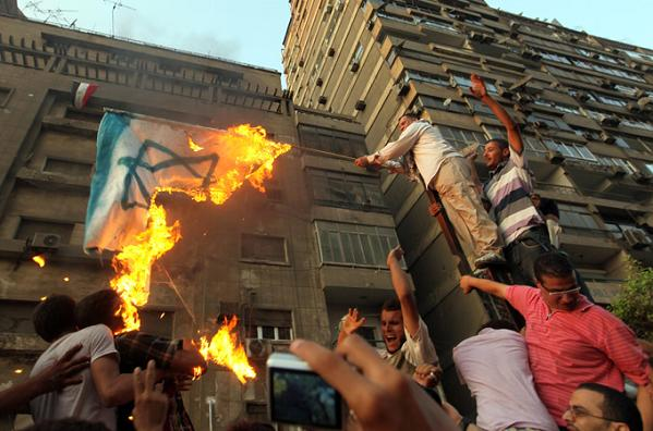 Egyptians protest outside the Israeli embassy in Cairo after tearing down a concrete protection wall nearby