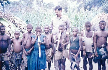 In July 1967 David Mendosa safaried to the Ruwenzori Mountains (between Uganda and the Congo) where he came across this group of Pygmies. David is the tall one.