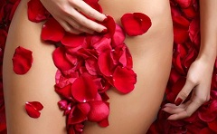 suntanned female body in petals of scarlet roses