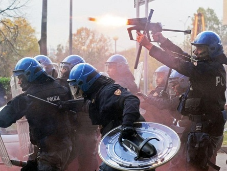 An officer fires tear gas as police face demonstrators during a protest against government austerity measures in Turin, Italy