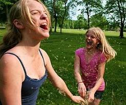 Happy Girls Playing In Dandelion Seeds Together