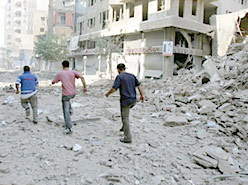 Lebanese terrorists heading away from a southern Beirut building destroyed by Israeli air strikes Friday. Reuters