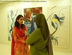 A very creative young artist, Sabahat Nawaz being interviewed by a news television channel. Her work titled 'Narcissism' in the background using the medium 'Fiber' (Fabric, thread and string on canvas) is on display at V.M Art Gallery. Karachi.