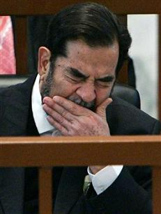 Ousted Iraqi President Saddam Hussein yawns while listening to the prosecution during the 'Anfal' genocide trial in Baghdad December 18, 2006. Prosecutors who accuse Saddam of genocide by ordering chemical attacks on Kurds produced documentary evidence at his trial on Monday in a new phase crucial to pinning down his personal responsibility.