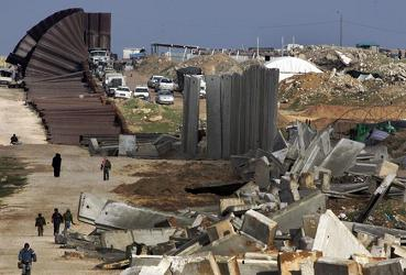 Palestinians pass by the destroyed part of the Egyptian-Gaza border in Rafah, southern Gaza Strip, January 31, 2008.