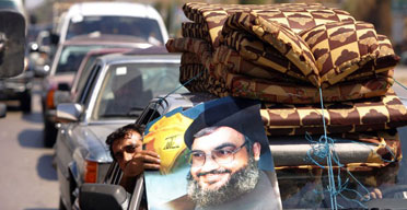 A displaced Lebanese man on his way home to south Lebanon displays a poster of the Hizbullah leader, Hassan Nasrallah. Photograph: Patrick Baz AFP /Getty Images