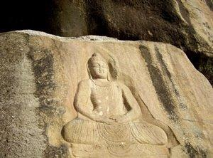 A survived statue of Buddha carved into a rock is seen in Jehanabad.