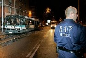 A French security public transport operator, from RATP, watches over the remains of a city bus Wednesday, Oct. 25, 2006, at the bus station of Nanterre, west of Paris. The bus was set on fire on Wednesday night in Nanterre by a gang of youths, after they forced passengers out. (AP)