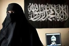 Malika El Aroud by her computer in her living room at her home in Brussels in April. The Arabic banner on the wall translates as: There is no God but Allah and Mohamed is his Messenger. (Hazel Thompson for the New York Times)