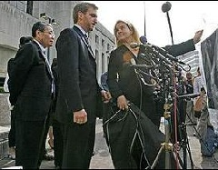 Jin Chung, left, with his legal team Chris Manning, and Mendi Sossamon, display the contentious pair of pants while delivering a statement to the media after the first day of Jin and Soo Chung's trial