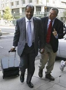 Administrative law judge Roy Pearson, left, is questioned by a member of the media as he leaves court after the second day of his lawsuit in Washington in this Wednesday, June 13, 2007 file photo.